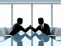 Businessmen arm wrestling. An illustration of the silhouettes of two men in business suits, arm wrestling at a table Stock Image