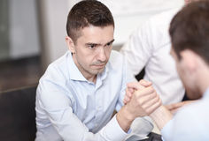 Businessmen arm wrestling in office Royalty Free Stock Photos