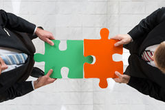 Businessmen Assembling Jigsaw Puzzle Representing Teamwork Stock Photo