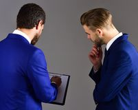 Businessmen assess the terms of the deal. ontracts and arrangem. Ents concept. Men in suit or businessmen with busy expression look at document or contract on royalty free stock images