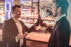 Businessmen in bar. Cheers! Young handsome businessmen in bar are drinking beer on a bar counter Royalty Free Stock Photo