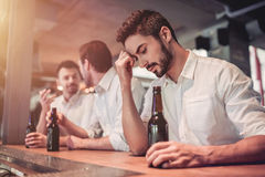 Businessmen in bar. Upset young businessman in bar is drinking beer on a bar counter Stock Photo