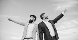 Businessmen bearded faces stand back to back sky background. Men formal suit managers pointing at opposite directions royalty free stock image