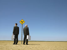 Businessmen With Briefcases Standing By Road Sign In Desert Stock Photography