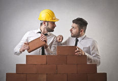 Businessmen building wall royalty free stock images