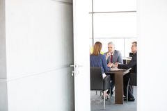 Businessmen and businesswoman in board room seen through open door at office Royalty Free Stock Image
