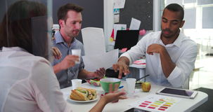 Businessmen And Businesswoman Having Working Lunch In Office stock video footage