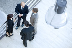 Businessmen and businesswoman standing together by railing Stock Photos