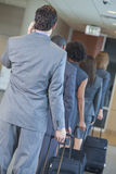 Businessmen Businesswomen Airport Traveling. Group or team of men and women, businessmen & businesswomen talking on cell phone and traveling in line through an Royalty Free Stock Photography