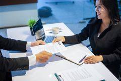 Businessmen and Businesswomen discussing documents for job inter stock image