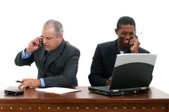 Businessmen on Cellphones at Desk Stock Image