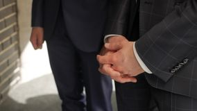 Businessmen chatting at the meeting. Two men in suits stand in front of the camera. One of them crossed his palms stock footage