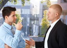 Businessmen chatting outside of office. Building, enjoying break royalty free stock photography