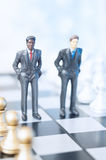 Businessmen on chessboard. Two toy businessmen, lawyers or politicians on a chessboard. Business, politics or law concept Stock Photos