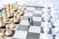 Businessmen on chessboard. Two  toy businessmen, lawyers or politicians on a chessboard. Agreement concept Stock Photo