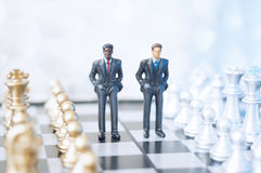 Businessmen on chessboard. Two toy businessmen, lawyers or politicians on a chessboard. Business, politics or law concept Stock Photo