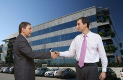 Businessmen closing a deal. Businessmen shaking hands in front of modern offices under a perfect blue sky royalty free stock photos