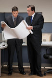 Businessmen collaborating over blueprints. In cubicle stock photography