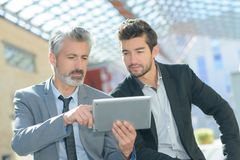 Businessmen with colleague holding tablet outside office. Business Stock Image