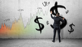 Businessmen on colorful profit chart background placing hands on a wall with black painted dollar signs and hand prints. Royalty Free Stock Photos