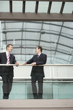 Businessmen Communicating While Standing Against Railing Royalty Free Stock Photo