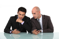 Businessmen comparing phones Stock Photos