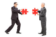 Businessmen connecting two pieces of puzzle Stock Photography