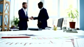 Businessmen contracted and shook hands. Focus on. Documentation. The camera moves from right to left. Graphs are arranged on the table stock video