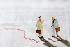 Businessmen in Conversation. Two miniature models of  standing over a red line graph Royalty Free Stock Photo