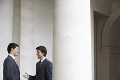 Businessmen Conversing By Pillar Stock Photo