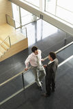 Businessmen Conversing By Railing In Office Royalty Free Stock Image