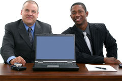 Businessmen at Desk with Laptop. Two businessmen and laptop facing camera.  Shot in studio over white Stock Image