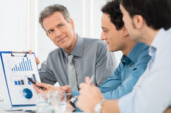 Businessmen Discussing Annual Report Chart. Portrait Of Mature Businessman Showing Annual Report Graph To His Colleague Royalty Free Stock Images
