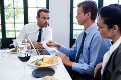 Businessmen discussing during a business lunch meeting Stock Photography
