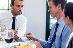 Businessmen discussing during a business lunch meeting Stock Images