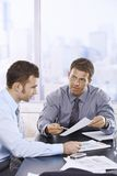 Businessmen discussing report Stock Photography