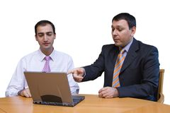 Businessmen discussing computer data. Two businessmen looking at a laptop computer; one pointing to some data. Isolated on white stock photo