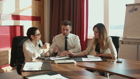 Businessmen discussing diagrams using laptop. Male and two females discussing diagrams using laptop stock footage