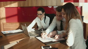 Businessmen discussing diagrams using laptop. Male and two females discussing diagrams using laptop stock video footage