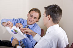 Businessmen discussing financial results Stock Photos