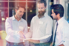 Businessmen discussing over blueprint Stock Image