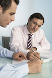 Businessmen Discussing Over Document At Desk Royalty Free Stock Photo