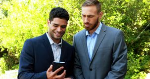 Businessmen discussing over mobile phone 4k. Businessmen discussing over mobile phone in park 4k stock video