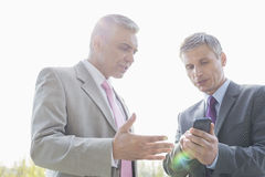 Businessmen discussing over mobile phone outdoors Royalty Free Stock Image