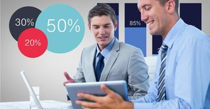 Businessmen discussing over tablet PC by graphs. Digital composite of Businessmen discussing over tablet PC by graphs Stock Photography