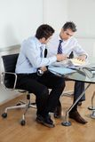 Businessmen Discussing Paperwork In Office Stock Photo
