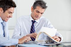 Businessmen Discussing Paperwork In Office Royalty Free Stock Images