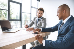 Businessmen discussing project during meeting at workplace with laptop. Multicultural businessmen discussing project during meeting at workplace with laptop Royalty Free Stock Images