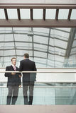 Businessmen Discussing While Standing Against Railing Stock Photos
