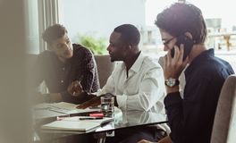Businessmen in a meeting. Businessmen discussing work sitting at conference table in office. Two men discussing work while another men is talking on mobile phone royalty free stock photography